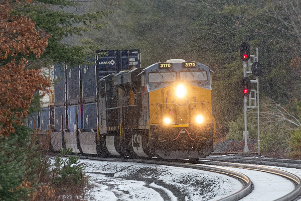 On a dismal, dark day, a very long Q022 works it's way through a snow shower at the S-curves at MP60 in Spencer MA.<br /> 12/14/2020