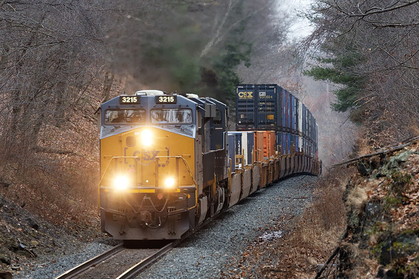 CSX train Q022 crests the top of the Charlton Hill near MP57 on the Boston Line.<br /> 1/13/2020