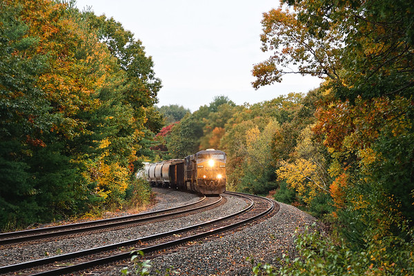 Even on a dark, rainy morning the early Fall colors seem to pop as train Q436 hits the S-curves at MP60 in Spencer MA.<br /> 10/12/2020