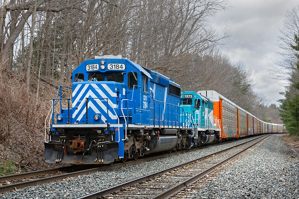 CEFX 3184 and EBSR 1272 pull a long drag of auto racks almost up to the bridge at East Brookfield.<br /> 4/10/2020