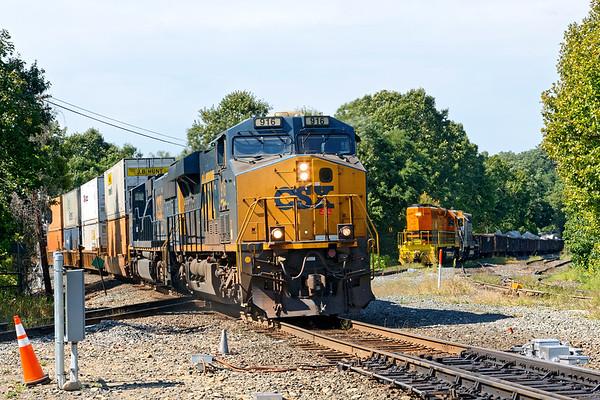 CSX train Q008 hustles into Palmer MA as NECR waits patiently to cross the diamond.<br /> 9/7/2020