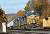 In early morning light, with a backdrop of Fall colors, CSX train Q012 rolls by MP83, just east of the diamond, in the CSX yard at Palmer, MA. 10/21/2012 - 598C3290dK