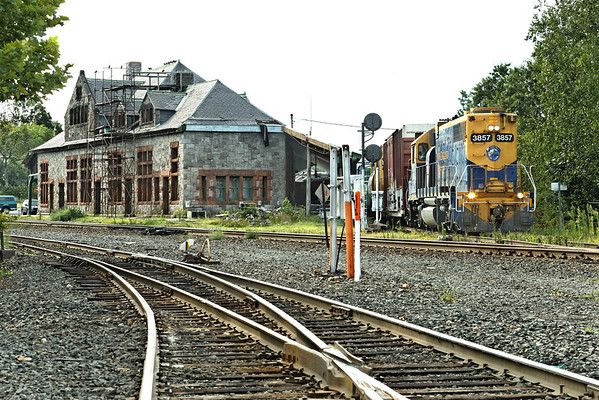 Just past the historic depot at MP83, Palmer, MA, NECR 3857 heads North out of their yard and across the CSX diamond with a short drag of mixed freight. 8/19/2012 - 598C0112dK