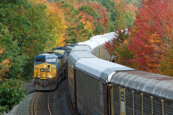 Tight squeeze - With early Fall color in the background, CSX train Q012 rolls past a line of auto racks on the siding in Spencer, MA on the CSX Boston Line. 10/02/2012 - 598C2625dK