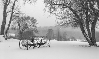 An old farm instrument on a farm in Lyme, on a snowy day.