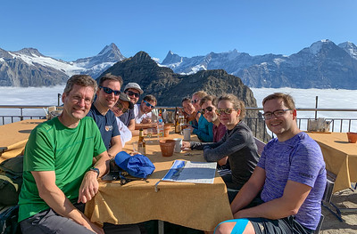 CDHI hikers enjoying sunshine and drinks at the summit of Faulhorn, with a view of the Berneralps over an undercast. Switzerland.
