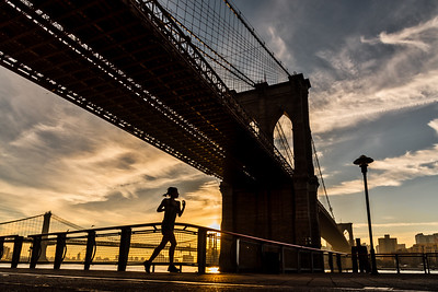 Jogging under the Brooklyn Bridge at sunrise.