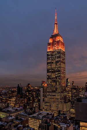 Empire State Building lit in Orange at dusk.