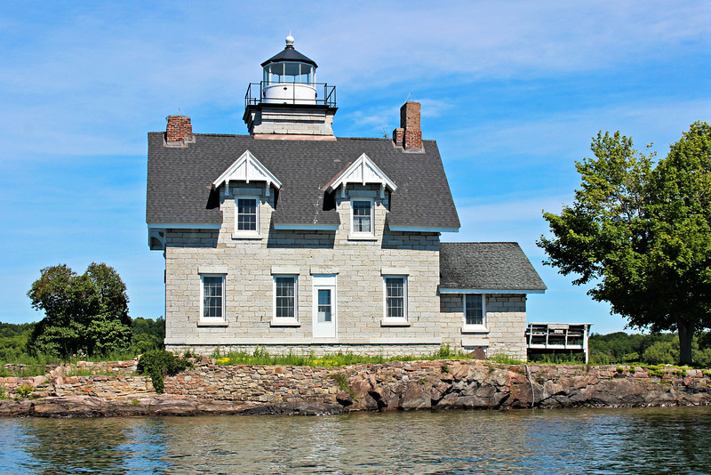 The original design for the Sister Islands Lighthouse called for the structure to be made of brick; however it was difficult to find quality brick, so the plans were revised to use dark gray limestone quarried in nearby Kingston, Ontario.  A two-story dwelling with a tower protruding from the middle of the roof was constructed on the easternmost island.  Wooden bridges were constructed to connect the three Sister Islands together.