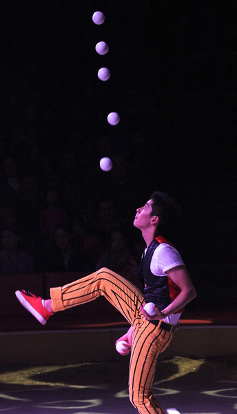 Ty Tojo, Big Apple Circus, November 30, 2013<br /> <br /> One of the unexpected benefits of parenthood is discovering fun events for the kids…that parents actually enjoy. Big Apple Circus has been an annual event in our family for the past seven years, one that my wife and I look forward to as much as our daughter. The circus is held every year in New York City at a tent at Damrosch Park at Lincoln Center. The venue is cozy, with only 16 rows of seats surrounding the ring and no seat more than 50 feet from ringside.<br /> <br /> This year's theme is Luminosity, a tribute to the real world circus of New York City's Times Square. The opening assembles the performers as members of this bustling city: construction workers, hot dog vendors, sign painters, corporate executives, surrounded by New York landmarks. For the next two hours, they transformed themselves from ordinary New Yorkers into extraordinary citizens of Gotham.<br /> <br /> The highlight of the show is construction workers Acro-Duo, (Ukrainian Vitaliy Prikhodko and Russian Alexei Anikine) performing hand-to-hand acrobatics. Alexei balances with one arm on the head of Vitaliy; in another part, Vitaliy stands straight while the Alexei is upside down in a straight body position, balancing on his partner's shoulders. Fifteen-year-old Ty Tojo is a hot dog vendor turned juggler, rapidly keeping seven balls in the air without a miscue. According to the Big Apple Circus website, Ty holds two Guinness Book of World Records for back juggling seven balls.<br /> <br /> The Mongolian Angels (Davaasuren Altantsetseg and Narangua Altankhuyag) transform themselves from corporate executives to double trapeze artists, swinging high above the ring. It wouldn't be New York without someone trying to swindle tourists from their money. Flimflam man Pierre Ginet was successful picking off a volunteer's wallet and watch. Ginet also deposits a real New York City rat into a trash bin, only to be transformed into a much larger rat the size of a pig (actually a capybara, the largest rodent in the world). Daniel Cyr from France is a sign painter who uses his ladder to perform remarkable balancing tricks and ultimately a back flip off of the unsupported ladder. And what would a circus be without animals? Jenny Vidbel performs with her dancing dogs and horses.<br /> <br /> The high wire act of Duo Guerrero (Werner Guerrero and Aura Cardinali) tip-toed up to a high perch; the team jump roped while balancing on the wire and balanced standing on a chair while the chair is supported by the wire. He also walks on the tightrope with his partner on his back, much of it while she sang. In a tense moment Saturday, he stumbled a bit while jump roping on the tightwire, but quickly regained his balance. The clown, Rob Torres performs in two segments spinning plates, juggling hats, interacting with the crowd.<br /> <br /> The last act was the Dosov Troupe, specializing in acrobatics using a seesaw type instrument to launch acrobats high into the air doing multiple twisting somersaults. Carrying the danger element one step further, one acrobat does back flips on stilts. This is a fast paced two hours of entertainment, with 18 segments and never a dull moment.<br /> <br /> The Big Apple Circus was founded in 1974 and is a not-for-profit performing arts institution. The troupe performs at Lincoln Center until January 12, then on to Alpharetta, Georgia from January 30-February 17, Bridgewater, NJ from February 27-March 16, Boston from March 25-May 11, and Queens from May 18-June 15.<br /> <br /> Photos<br /> <br /> The Big Apple Circus is photography friendly, allowing photos but no flash or video. I used a Canon T2i with a 70-200mm f4L non-IS zoom. The T2i is a mid-level somewhat compact DSLR designed and priced for consumers rather than professionals. I sat on the side of the ring and the lighting conditions were challenging due to the darkness and contrasting light. Most of the photos were at 3200 ISO with a shutter speed between 1/250-1/320. With 3200 ISO, the photos were a bit grainy, so I used Topaz de-noise software. Overall, shots of slowly moving objects turned out fine. However, shots of fast moving acrobats doing somersaults were blurry and generally out of focus. I would think that a more responsive sports camera would shine in the dim light with fast moving objects, with higher ISO and greater autofocus capabilities. I guess that's why a professional camera like the Canon EOS 1 DX costs $6,800 (body only) and a 70-200  f2.8L IS retails for $2,500 over my equipment (about $600 for the T2i and $700 for the 700-200 f4L).