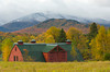 A red barn in the Adirondack Mountains with fall foliage color in New York State, USA.