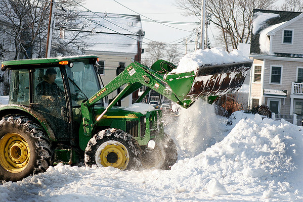 Newburyport: Local residents continue to dig out from the storms of this past weekend. Here, a front loader removes snow from a driveway on Water Street and piles it up next to the sea wall. Photo by Ben Laing/Newburyport Daily News Monday December 22, 2008.