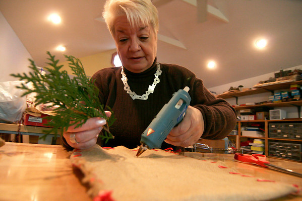 Newbury: Paula Wright decorates a home made gift bag wiith some evergreen branches at her home in Newbury. Photo by Ben Laing/Newburyport Daily News Monday December 15, 2008.
