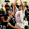 Newburyport:<br /> Clipper's Denis Ipbuken sails for two points as Triton's Ben Cross defends.<br /> Photo by Bryan Eaton/Newburyport Daily News Tuesday, December 16, 2008