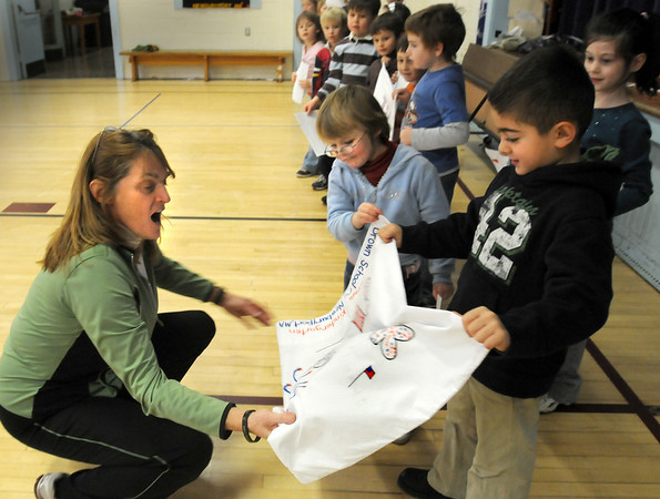 """Newburyport:<br /> Brown School physical education teacher Cathy Hill reacts as children in Dianna Ouellette's kindergarten class present her with decorated pillowcases and letters for her son, Marine Sgt. Michael Hill who is serving his third tour in Iraq and won't be home for Christmas. The """"Pillowcase Project"""" has special meaning for Ouellette as her sister-in-law, Sue Hines, mother of slain soldier Derek Hines, sent freshly washed pillow cases to him while serving in Afghanistan.<br /> Photo by Bryan Eaton/Newburyport Daily News Tuesday, December 09, 2008"""