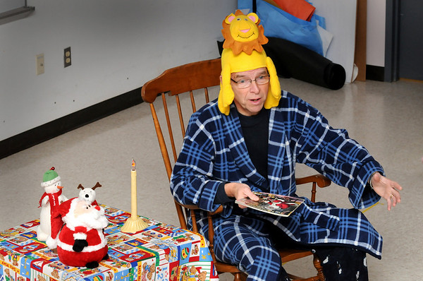"Amesbury:<br /> Cashman School principal Peter Hoyt read "" 'Twas the Night Before Christmas"" to kindergartners at the Amesbury school on Wednesday while wearing his pajamas and a lion hat. It was Pajama Day for kindergarters and Weird Hat Day for the whole school.<br /> Photo by Bryan Eaton/Newburyport Daily News Wednesday, December 17, 2008"