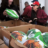 Amesbury:<br /> Volunteer Stefanie McCowan of the Amesbury Chamber of Commerce, left, hands a frozen turkey to Sue Robinson of Amesbury at Our Neighbor's Table on Wednesday afternoon. The agency was able to replace their ham and turkey supplies to be given away which had been thawed after power from last week's storm was cut to their freezers.<br /> Photo by Bryan Eaton/Newburyport Daily News Wednesday, December 17, 2008
