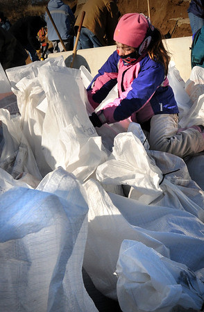 Newbury:<br /> Tegan Murray, 8, of Plum Island is bundled against Saturday's cold wind as she ties up sand bags other volunteers have filled.<br /> Photo by Bryan Eaton/Newburyport Daily News Saturday, December 13, 2008