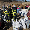 Newbury:<br /> Scores of volunteers filled sandbags in the cold weather on Olga Way on Plum Island.<br /> Photo by Bryan Eaton/Newburyport Daily News Saturday, December 13, 2008