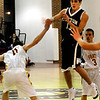 Newburyport:<br /> Triton's Collin Smith throws the ball over a defending Joe Clancy last night at Newburyport High School.<br /> Photo by Bryan Eaton/Newburyport Daily News Tuesday, December 16, 2008