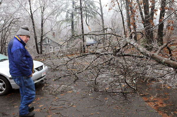 Amesbury:<br /> Dave Perley checks out the downed limbs and power lines on Cross Street in Amesbury.<br /> Photo by Bryan Eaton/Newburyport Daily News Friday, December 12, 2008