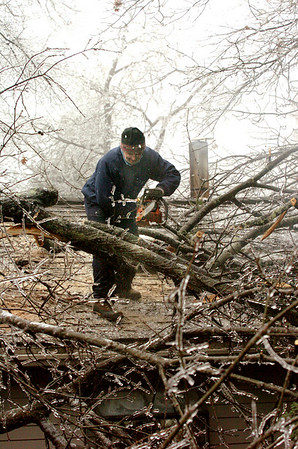 Amesbury:<br /> Larry Benjamin kept a sense of humor talking to neighbors as he cut branches of a limb that landed on his home on First Street in Amesbury puncturing the roof in several spots.<br /> Photo by Bryan Eaton/Newburyport Daily News Friday, December 12, 2008