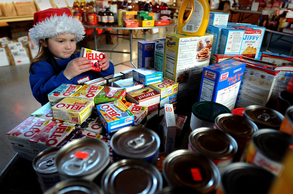Newburyport:<br /> Katherine Quinn, 4, of Newburyport lines up boxes of Jell-O, while volunteering at the Salvation Army on Tuesday. The organization was giving out food and Christmas presents the had collected for qualifying families.<br /> Photo by Bryan Eaton/Newburyport Daily News Tuesday, December 23, 2008