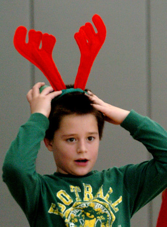 """Salisbury:<br /> Ryan Farrell, 9, adjusts his reindeer antlers which kept falling off yesterday morning at Salisbury Elementary School. He was in gym class playing an indoor """"snowball"""" game which is similar to dodgeball and uses small foam balls.<br /> Photo by Bryan Eaton/Newburyport Daily News Tuesday, December 23, 2008"""