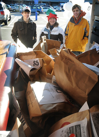 Newburyport: Volunteers Doug Sauter, Amy Goutier, and Ryan Clark look over a police truck filled with food collected by the Newburyport Police Saturday at Shaws in Newburyport. The police also collected food at the Market Basket.photo by Jim Vaiknoras/Newburyport Daily News/Saturday December 13, 2008