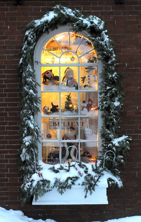 """Newburyport: """"In the air there's a feeling of Christmas"""" The holday decorations in the window of the Dragon's Nest toy store in Market Square is framed by snow and a graland of evergreens.photo by Jim Vaiknoras/Newburyport Daily News.Sunday December 21, 2008"""