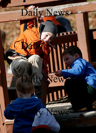 Amesbury: Alfred Arcidi, 3, of East Kingston (organge jacket) monkey's around on the jungle gym at the Amesbury town park Monday morning. Photo by Ben Laing/Newburyport Daily News Monday November 10, 2008.