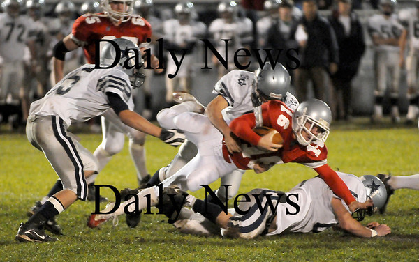 Amesbury: Indians quarterback Jared Flannigan (16) is tripped up by defenders from Hamilton-Wenham during Friday nights game at Landry Stadium. Photo by Ben Laing/Newburyport Daily News Friday November 7, 2008.