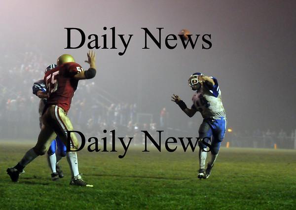 Newburyport: Royals quarterback Joe Esposito (14) throws a pass on the run while Newburyport's Dennis Ipbuken (55) closes in during Friday night's game at NHS. Photo by Ben Laing/Newburyport Daily News Friday November 14, 2008.