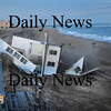 Newbury:<br /> The house at 16R Northern Boulevard on Plum Island is toppled onto the beach by heavy equipment hidden from view.<br /> Photo by Bryan Eaton/Newburyport Daily News Wednesday, November 26, 2008