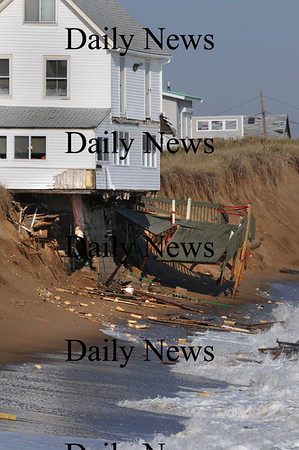 Newbury:<br /> The deck hangs off the house at 16R Northern Boulevard as waves crash strewing debris about.<br /> Photo by Bryan Eaton/Newburyport Daily News Wednesday, November 26, 2008
