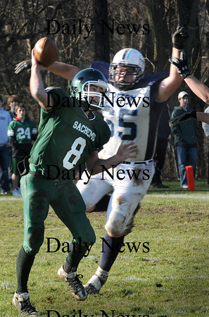 West Newbury:<br /> Triton's Pat Carney tries to block a throw by Pentucket quarterback Jordan Silva.<br /> Photo by Bryan Eaton/Newburyport Daily News Thursday, November 27, 2008
