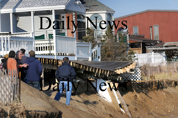 Newbury:<br /> People watch a house in danger of falling further down the beach at Plum Island center, standing next to Jeanne's which deck has also collapsed.<br /> Photo by Bryan Eaton/Newburyport Daily News Wednesday, November 26, 2008