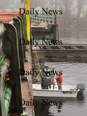 Amesbury:<br /> Inspectors check out the base of the Derek Hines Bridge yesterday morning which is closed after being hit by a barge on Thursday.<br /> Photo by Bryan Eaton/Newburyport Daily News Friday, November 14, 2008