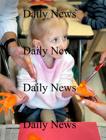 Salisbury:<br /> Stacy Peace, 3, gets her hands painted in Maureen Winn's preschool class at Salisbury Elementary School on Wednesday morning. The children were creating pictures of turkeys by pressing the painted hands onto paper to look like the feathers of the bird.<br /> Photo by Bryan Eaton/Newburyport Daily News Wednesday, November 12, 2008
