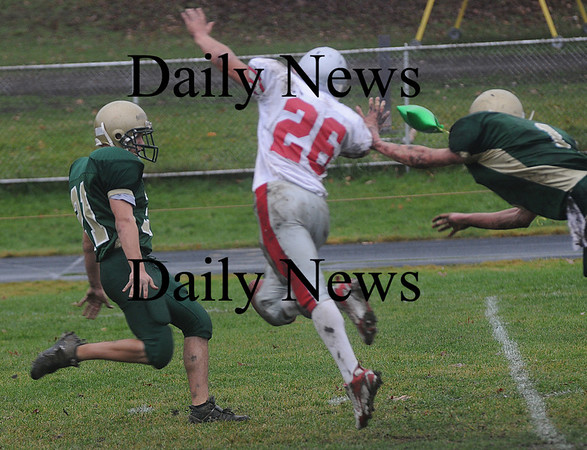 North Reading: North Reading punter Gregory Bugli just gets off a kick while being pressured by Amesbury's Jesse Burell during their game at North Reading Saturday. photo by Jim Vaiknoras/Newburyport Daily News, Saturday November 15, 2008
