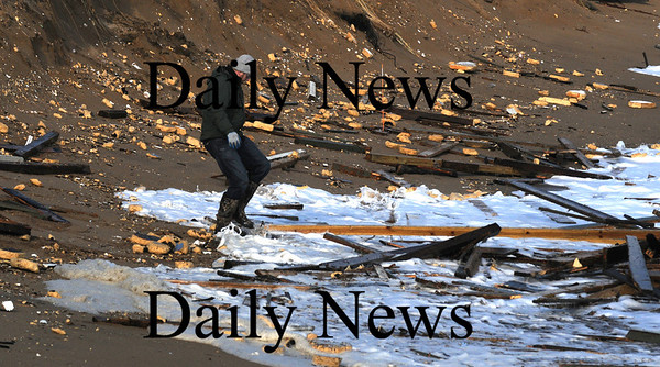 Newbury:A unidentified man looks though the debris along Plum Island. Waves under cut sand at house on causing it to tilt towards the ocean. photo by Jim Vaiknoras/Newburyport Daily News, Wednesday November 26, 2008