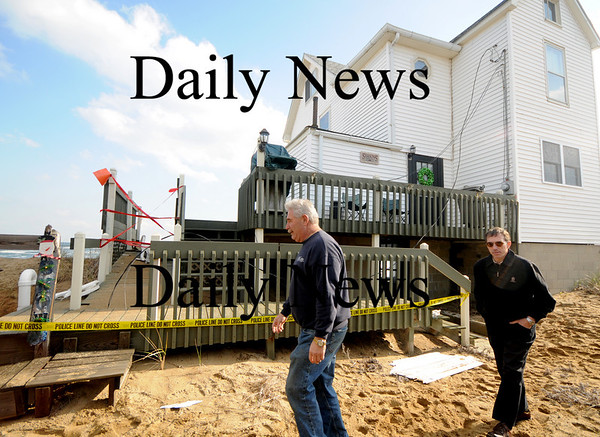 Newbury: Ron Barrett and Wayne Capolupo check out damage to a home on Plum Island. Waves under cut sand at house on causing it to tilt towards the ocean. photo by Jim Vaiknoras/Newburyport Daily News, Wednesday November 26, 2008