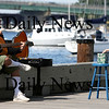 Newburyport: Young Tommy Finnerty of Newbury slips some money into Jesse Walker's box as he plays his guitar along the boardwalk Wednesday afternoon. Photo by Ben Laing/Newburyport Daily News Wednesday September 17, 2008.