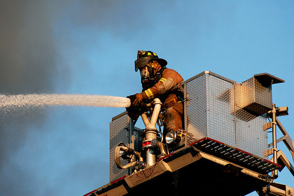 Merrimac: A local firefighter adjusts a hose from high atop a ladder truck as a fire raged through a shopping plaza on Rt. 110 in Merrimac. Photo by Ben Laing/Staff Photo