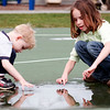 Newburyport: Ryan Nolan, 3, and Chalee Welch, 7, of Salisbury, play in a puddle at Cashman Park in Newburyport Wednesday morning. Photo by Ben Laing/Staff Photo