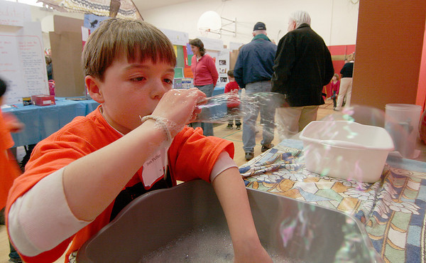 Newburyport: Bresnahan Elementary student Ben Peffer experiments with different types of soap to see which makes the best bubbles during the school's science fair Thursday night. Photo by Ben Laing/Staff Photo