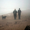 Newbury: A pair of dogs take a stroll down Plum Island with their owners Tuesday morning, despite the thick fog. Photo by Ben Laing/Staff Photo