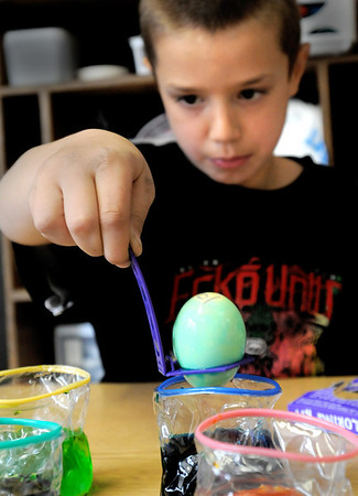 Amesbury:<br /> Chase Turner, 7, carefully removes an egg from a colored solution in Cathy Patten's class at Amesbury Elementary School on Wednesday afternoon. Parent volunteer Cheryl Miller, whose son, George, 8, is in the class, came in to make the Easter eggs with the students.<br /> Photo by Bryan Eaton/Newburyport Daily News Wednesday, April 01, 2009