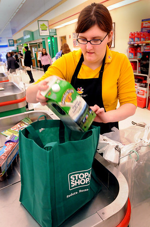 "Amesbury:<br /> Ashley Griffin, 16, puts groceries into a reusable bag, next to a pack of plastic bags at Stop and Shop in Amesbury on Tuesday afternoon. Many supermarkets are now pushing the bags as a cost-cutting move and a way to be more ""green.""<br /> Photo by Bryan Eaton/Newburyport Daily News Tuesday, April 07, 2009"