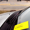 Newburyport:<br /> A warning ticket sits on the windshield of one of a dozen cars ticketed on Parker Street as a near-empty train station parking lot is seen in the back. Many commuters are parked along the street and Boston Way instead of paying to park in the train lots.<br /> Photo by Bryan Eaton/Newburyport Daily News Wednesday, April 01, 2009